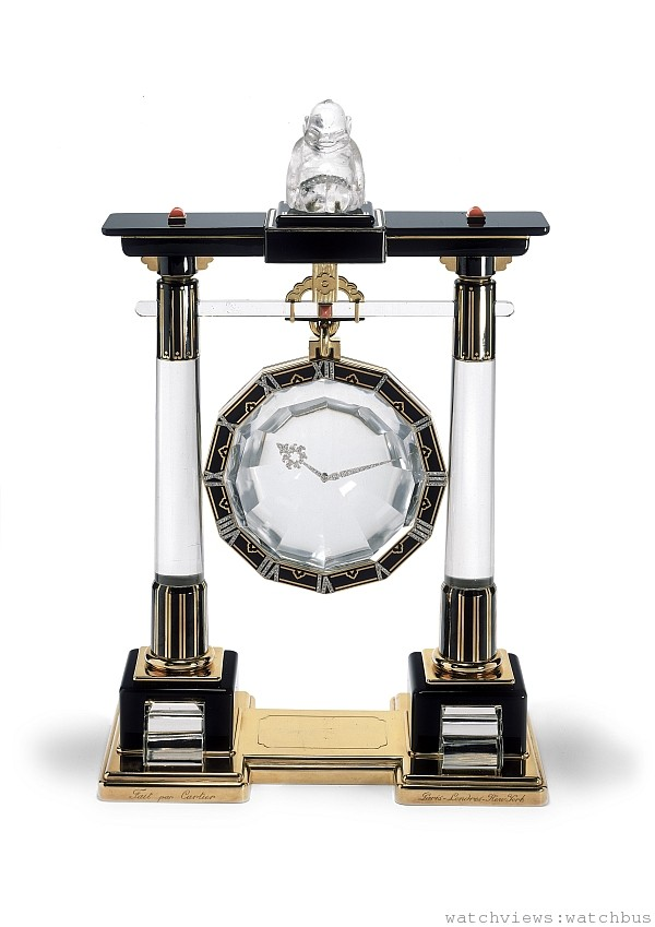 「門廊」神秘鐘,1923年,卡地亞巴黎。K金,鉑金,天然水晶,珊瑚,縞瑪瑙,玫瑰式切割鑽石;8天動力儲存方形機芯,雙發條盒,鍍金,13枚寶石軸承,瑞士槓桿式擒縱結構,雙金屬擺輪,寶璣擺輪游絲。 傳動軸隱藏在天然水晶橫桿上的凸圓形珊瑚後。移開福神雕像即可看到機芯 上鏈匙調校時間和上鏈。這款時鐘是一套日本道教「門廊」形時鐘中的第一款。全套時鐘共有六款,每一款都各不相同,由卡地亞在1923-1925年之間創作。