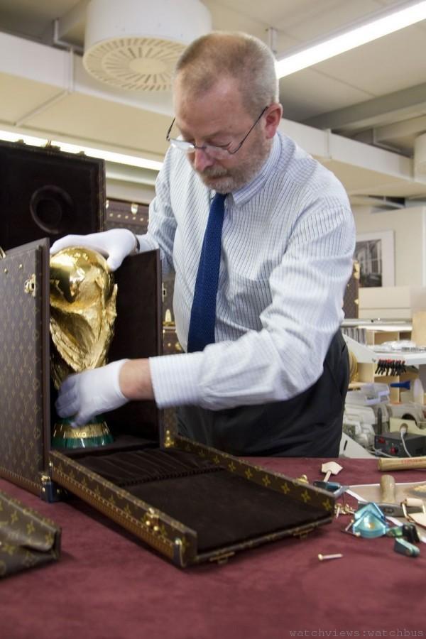 路易威登第五代傳人 Patrick Louis Vuitton慎重地將世足金盃放進路易威登硬殼箱中。