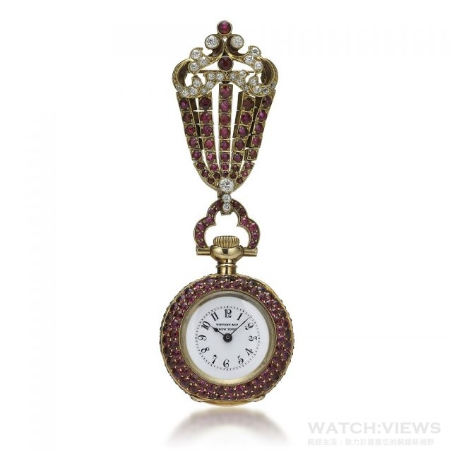Tiffany 翻領錶 (Lapel Watch,1895年作品)以黃金、紅寶石與鑽石嵌鑲而成的翻領錶,金質獵錶殼搭載Cresaux Watch Co. 機芯。白色琺瑯瓷錶盤搭配阿拉伯數字時標與不鏽鋼鍬形二段式指針。錶體密釘鋪鑲紅寶石,供其垂掛的胸針鑲有渦狀造型鑽飾,富延展性的黃金鑲紅寶石串鍊,下方一只鑽石掛鉤用來固定錶體,胸針採用的造型很容易讓人聯想起昔日的軍事王權。