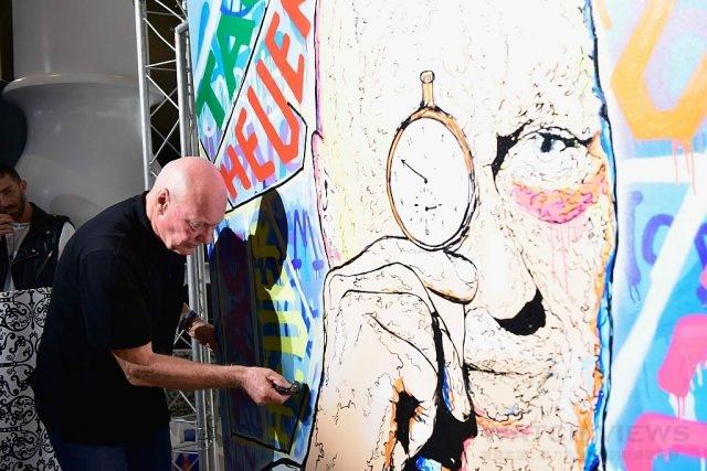 TAG Heuer執行長Jean-Claude Biver在Alec Monopoly為其肖像畫作上留下簽名。
