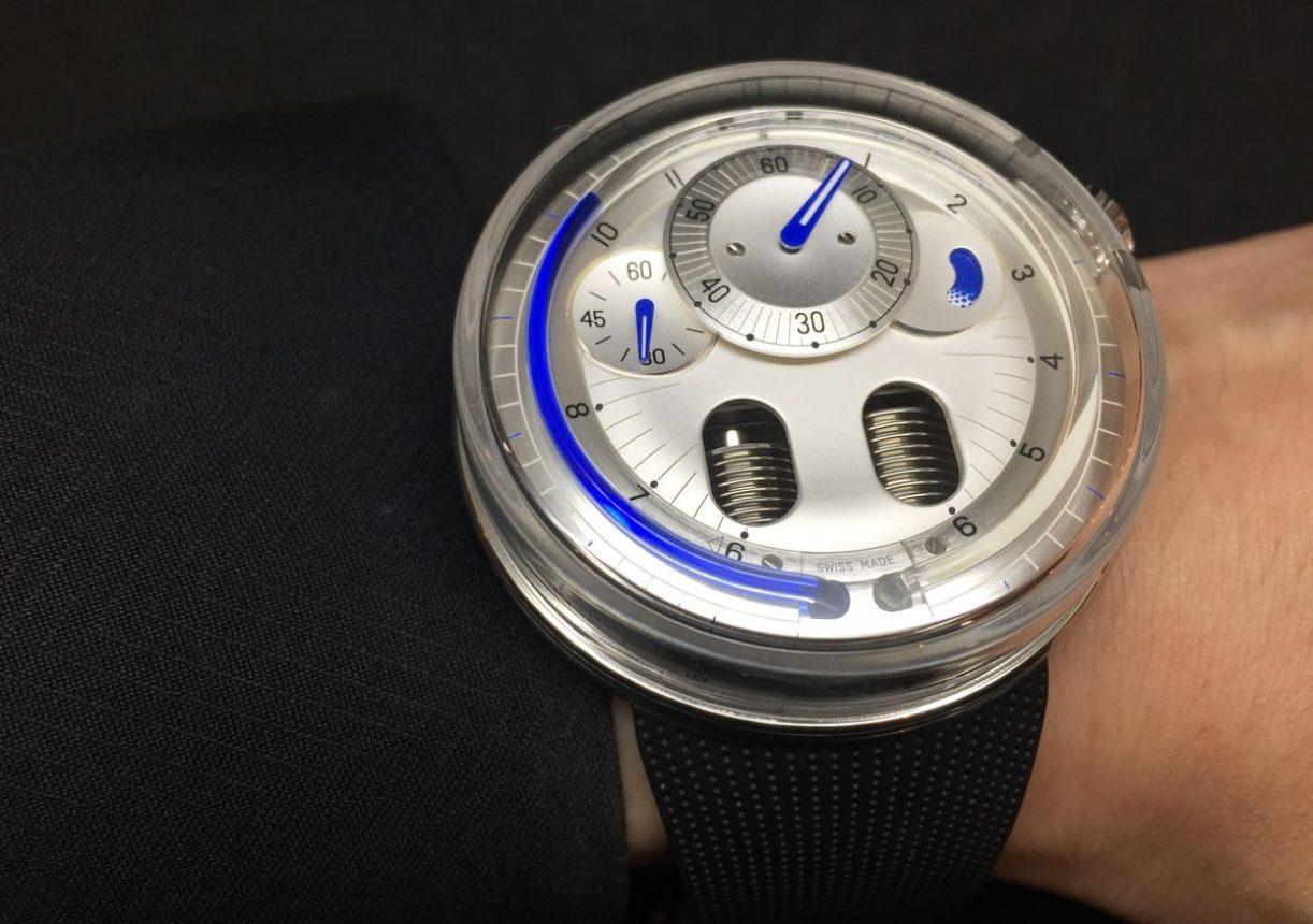 H0,鈦金屬錶殼,錶徑48.8毫米,逆跳式流體小時、偏心分鐘、小秒針、動力儲存顯示,手動上鍊機芯,動力儲存65小時,藍寶石水晶玻璃鏡面及底蓋,防水30米,橡膠錶帶,限量15只,參考價:NTD 1,380,000。